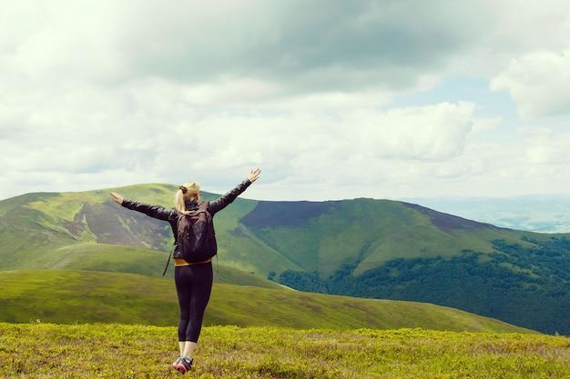 Jovem de pé na borda do penhasco e olhando para um amplo vale