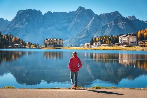 Jovem de pé na costa do lago misurina ao nascer do sol no outono