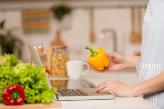Jovem de pé na cozinha com o laptop e procurando receitas. conceito de comida. fechar-se.