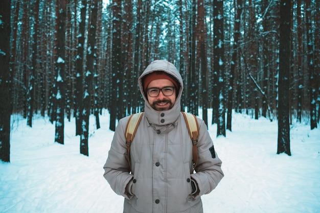 Jovem de pé na floresta de inverno nevado