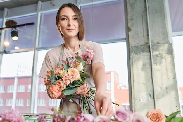 Jovem de pé na frente da câmera enquanto trabalhava em floricultura e fazendo buquê de rosas