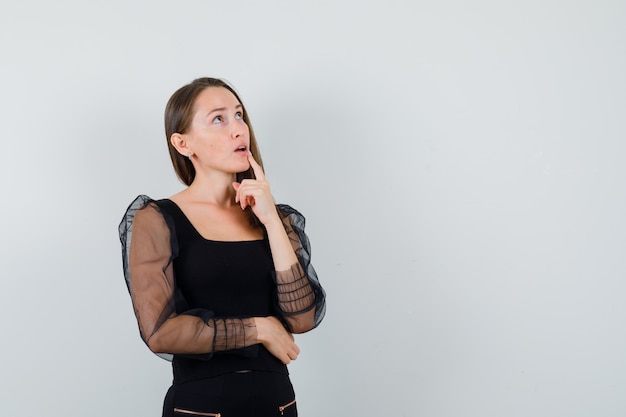 Jovem de pé na pose de pensamento de blusa preta e calça preta e olhando pensativa, vista frontal.