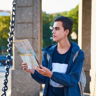 Jovem de pé na rua da cidade grande e olhando para o guia, um turista em são petersburgo