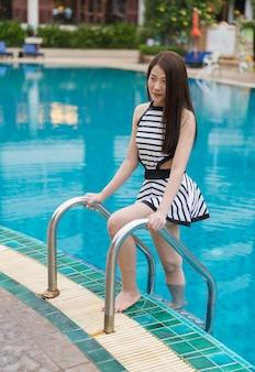 Jovem de pé nas escadas da piscina