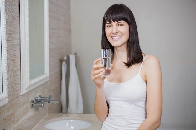 Jovem de pé no banheiro segurando o copo de água