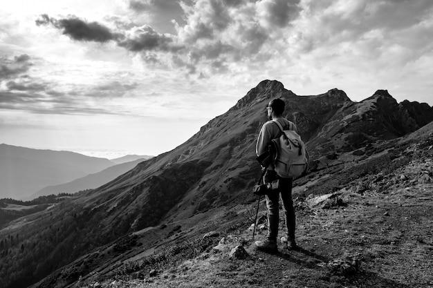 Jovem de pé no topo de montanhas do penhasco
