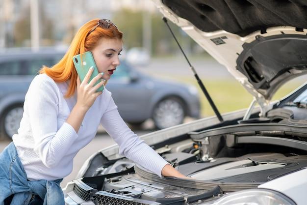 Jovem de pé perto de carro quebrado com capuz estalado, falando em seu telefone celular enquanto aguarda ajuda.