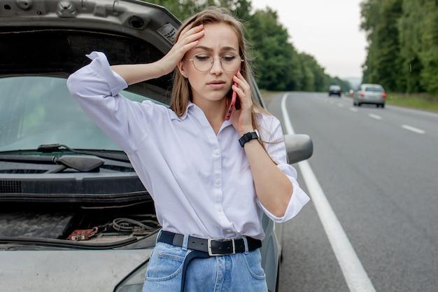 Jovem de pé perto de um carro quebrado com capô estourado, tendo problemas com seu veículo.
