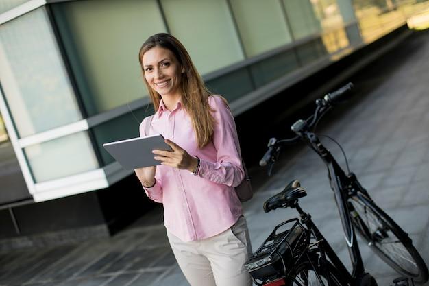 Jovem de pé por uma bicicleta elétrica e usando tablet digital em ambiente urbano