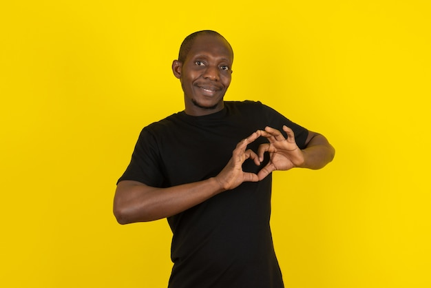 Jovem de pele escura fazendo gesto de coração na parede amarela
