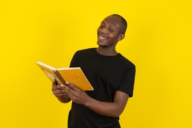 Jovem de pele escura lendo livro interessante na parede amarela