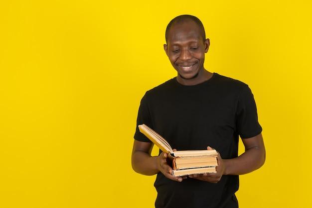 Jovem de pele escura segurando um livro e lendo na parede amarela