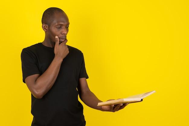 Jovem de pele escura segurando um livro e pensando na parede amarela
