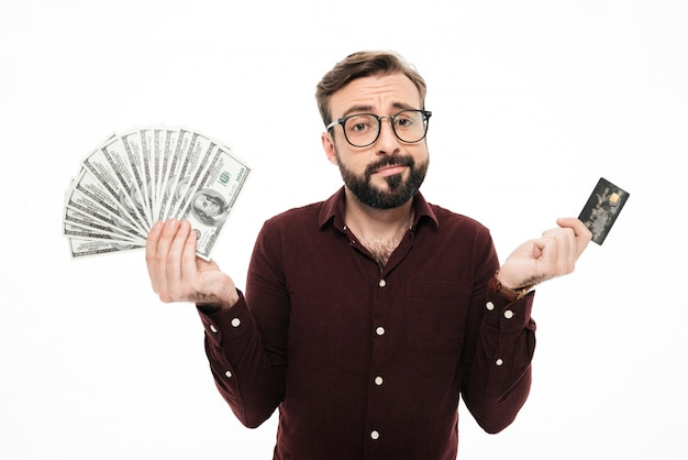Jovem de pensamento confuso, segurando o dinheiro e cartão de crédito.