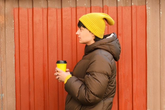 Jovem de perfil com chapéu de malha amarelo e roupas de outono com uma xícara de café nas mãos