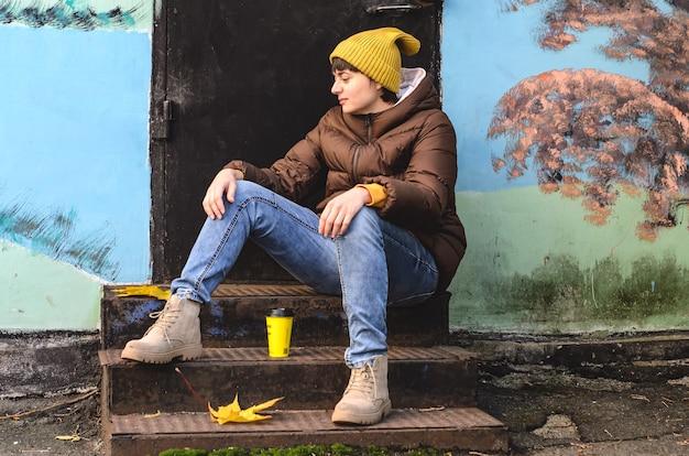 Jovem de perfil com chapéu de malha amarelo e roupas de outono com uma xícara de café sentada em degraus de metal