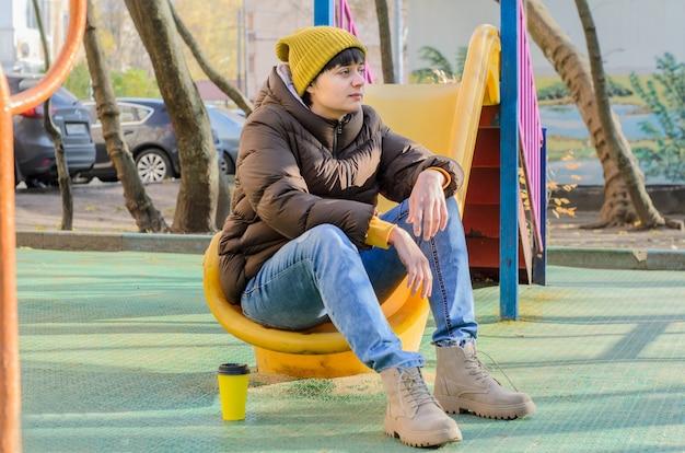Jovem de perfil com chapéu de malha amarelo e roupas de outono com uma xícara de café sentada na cidade