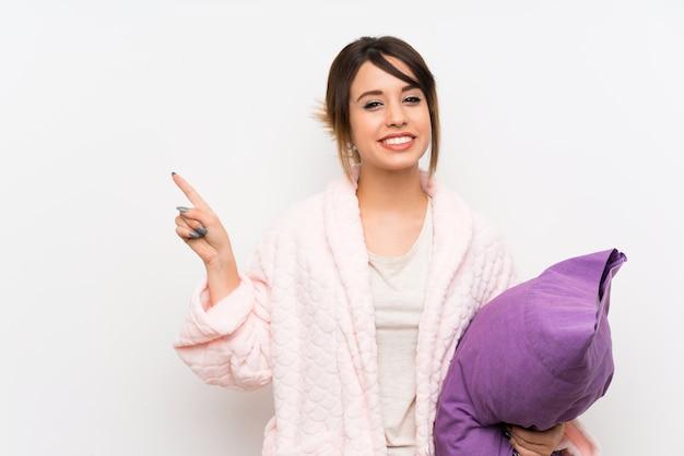 Jovem de pijama com roupão apontando para o lado para apresentar um produto