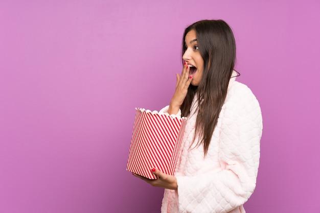 Jovem de pijama e roupão sobre parede roxa isolada segurando pipocas