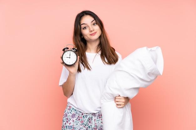 Jovem de pijama e segurando o relógio vintage isolado na parede rosa