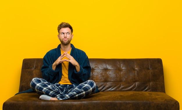 Jovem de pijama, planejando e conspirando, pensando em truques e truques desonestos, astúcia e traição. sentado em um sofá