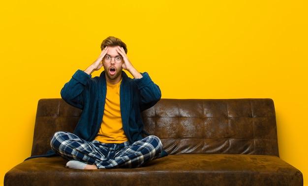 Jovem de pijama se sentindo horrorizado e chocado, levantando as mãos na cabeça e entrando em pânico por um erro