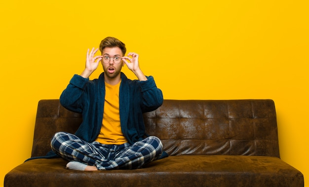 Jovem de pijama, sentindo-se chocado, surpreso e surpreso, segurando os óculos com um olhar atônito e incrédulo. sentado em um sofá