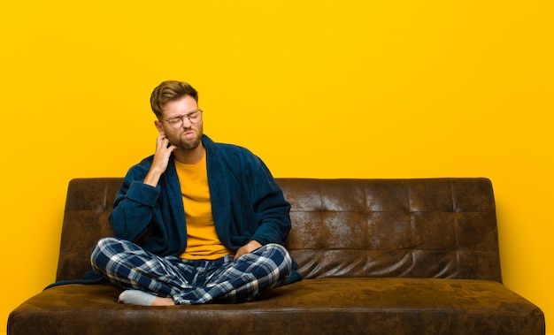 Jovem de pijama, sentindo-se estressado, frustrado e cansado, esfregando o pescoço doloroso, com um olhar preocupado e preocupado. sentado em um sofá