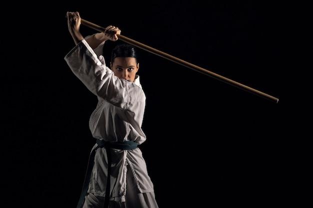Jovem de quimono praticando com jodo em um fundo preto