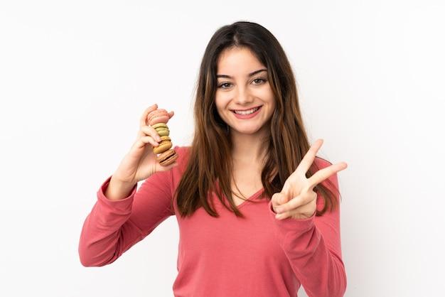 Jovem de rosa segurando macarons franceses coloridos e mostrando sinal de vitória