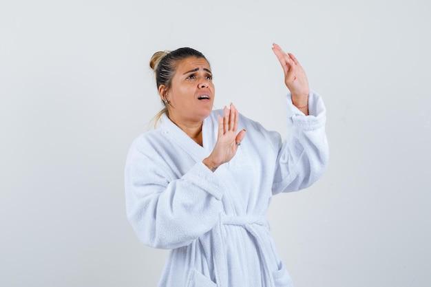 Jovem de roupão de banho, de mãos dadas, em pose de defesa e parecendo assustada