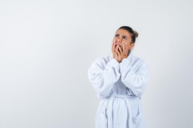 Jovem de roupão de banho segurando o rosto com as mãos e parecendo pensativa