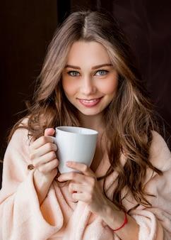 Jovem de roupão macio rosa bebe chá e sorrindo.