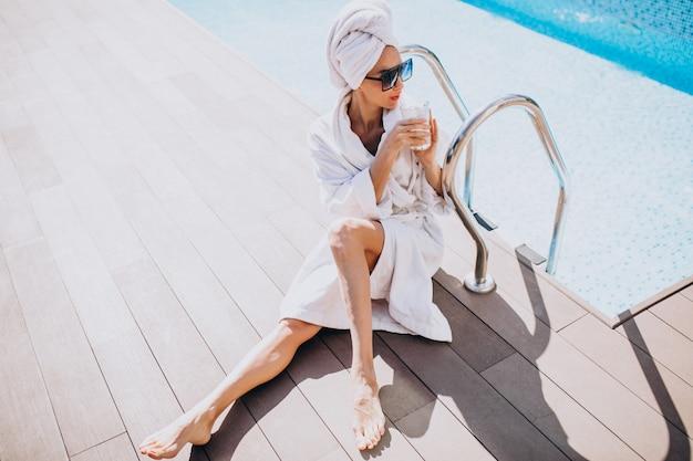 Jovem de roupão tomando café à beira da piscina