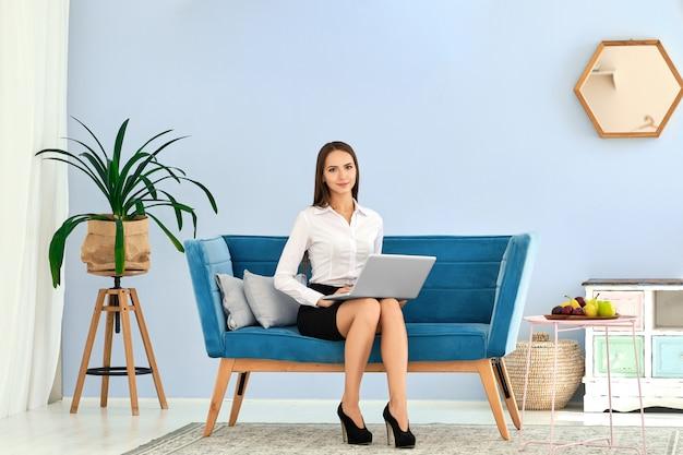 Jovem de saia preta e blusa branca, usando laptop enquanto está sentado no sofá confortável