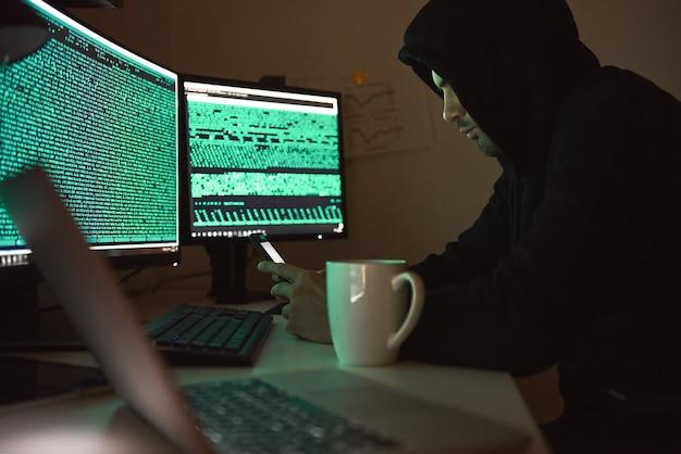Jovem de segurança de computador com capuz preto usando vários computadores e seu smartphone para roubar
