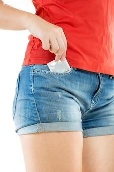Jovem de short tirando preservativo embalado