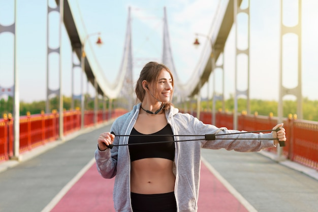 Jovem, de sportswear preto e fones de ouvido, está fazendo manhã alongamento exercícios com elástico. garota está fazendo exercícios na ponte urbana pedonal na cidade. conceito de estilo de vida saudável e desportivo.