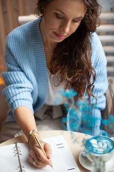 Jovem de suéter azul quente sentada perto da grande janela da cafeteria e escrevendo uma lista de compras de natal com uma xícara de café com leite azul. planejando as férias de natal. conceito de organização e planejamento.