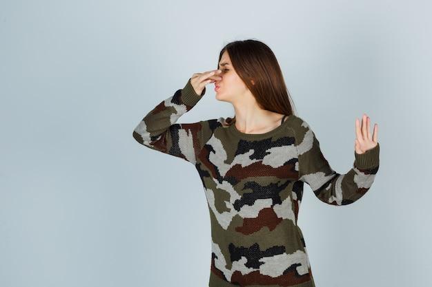 Jovem de suéter beliscando o nariz devido ao mau cheiro e parecendo enojada