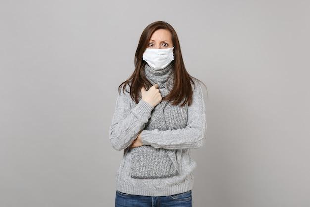 Jovem de suéter cinza, lenço com máscara facial estéril isolada no fundo da parede cinza, retrato de estúdio. estilo de vida saudável, tratamento de doença doente, conceito de estação fria. simule o espaço da cópia.