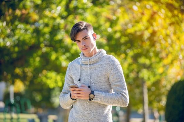 Jovem de suéter cinza no parque com telefone celular e fones de ouvido