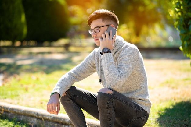 Jovem de suéter cinza no parque sobre falar ao telefone e beber café. copyspace