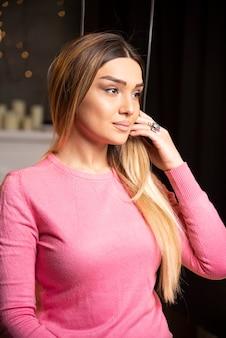 Jovem de suéter rosa olhando para longe e posando. foto de alta qualidade