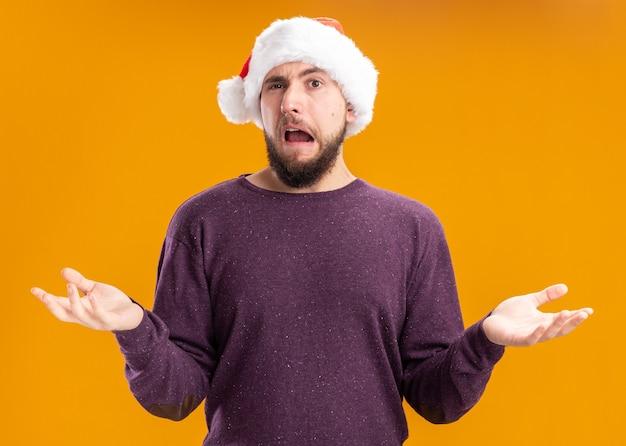 Jovem de suéter roxo e chapéu de papai noel confuso e descontente com os braços abertos para os lados, em pé sobre a parede laranja