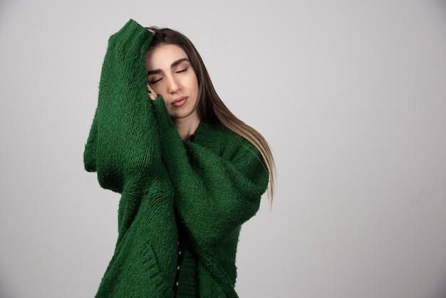 Jovem de suéter verde dormindo na cinza.