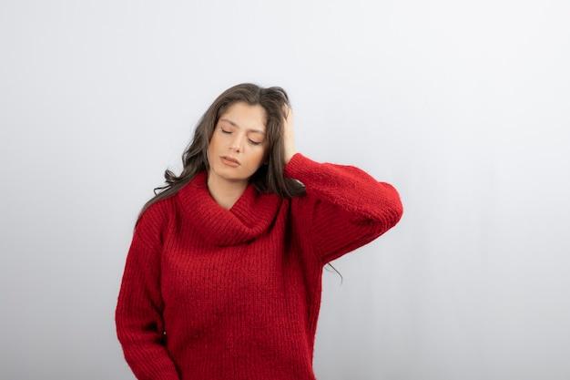 Jovem de suéter vermelho quente, sofrendo de dor de cabeça.