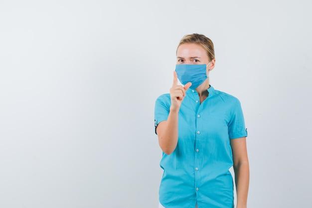 Jovem de t-shirt, máscara a ameaçar com o dedo e a parecer séria Foto gratuita