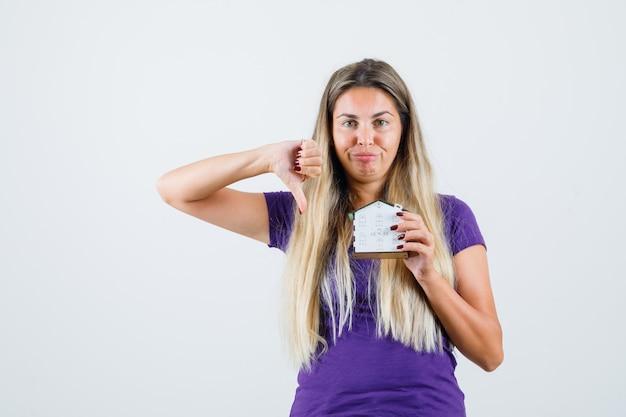 Jovem de t-shirt violeta, segurando o modelo da casa, mostrando o polegar para baixo e olhando o descontentamento, vista frontal.