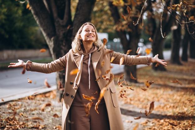 Jovem de terno bege fora em um parque de outono